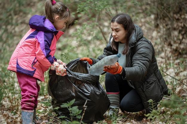 Mama und tochter säubern den wald von plastik und anderem schmutz