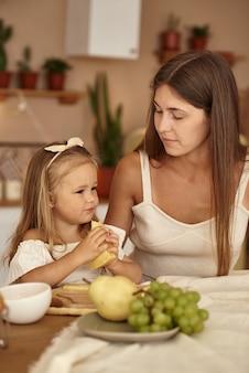 Mama und tochter sitzen in der küche und essen ein stück käse.