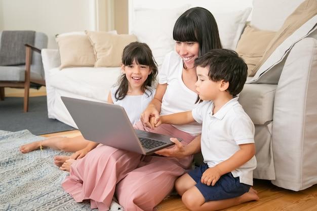 Mama und zwei kinder schauen sich einen lustigen film an, während sie im wohnzimmer auf dem boden sitzen, einen laptop benutzen und lachen.