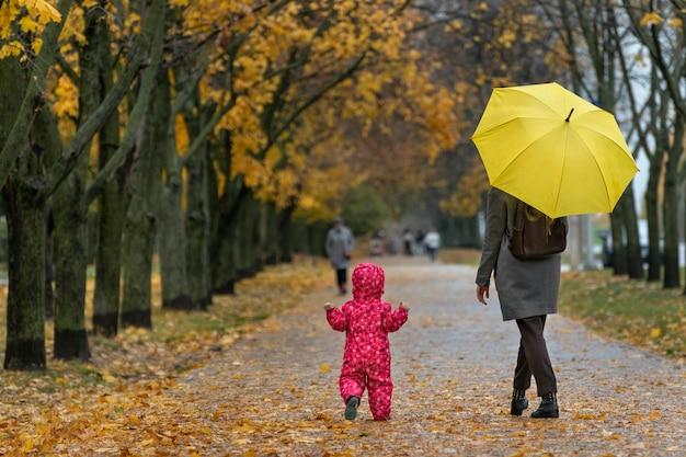 Mama unter einem gelben regenschirm und baby gehen eine gasse mit gefallenen blättern durch einen herbstpark entlang.