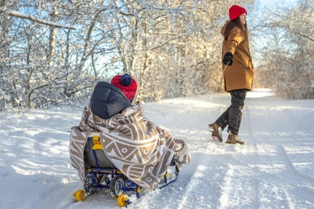 Mama zieht ein kind auf einem schlitten, der an einem frostigen winter läuft. sonniger tag im freien