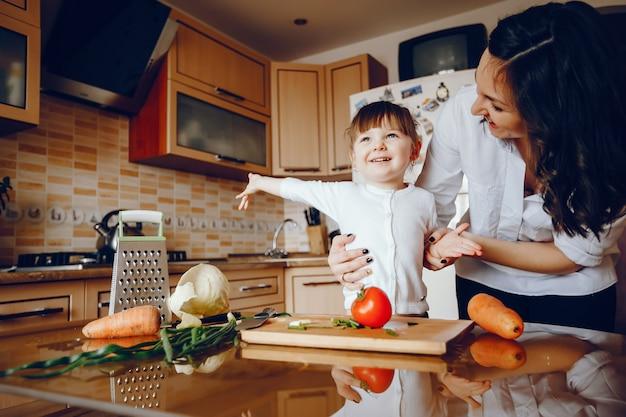 Mama zusammen mit ihrer tochter kocht gemüse zu hause in der küche