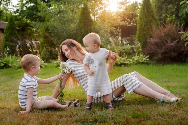 Mama, zwei kinder ruhen auf der natur. rivalität unter geschwistern. brüder, mutterschaft.