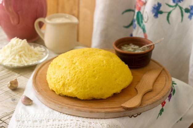 Mamaliaga oder polenta, ein traditionelles gericht der moldauischen, rumänischen, ungarischen und ukrainischen küche. brei aus maismehl. serviert mit brynza, sauerrahm und knoblauchsauce.