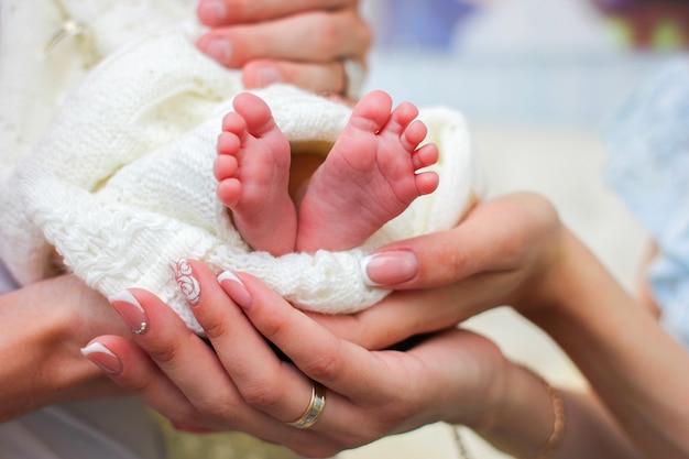 Mamas hände halten die kleinen beine ihres neugeborenen, eingehüllt in eine weiße warme decke