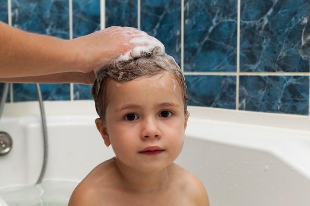 Mamas hände waschen den kopf des kleinen mädchens im badezimmer. das symbol für reinheit und hygieneausbildung.
