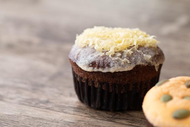 Mamon-kuchen oder -kleiner kuchen auf hölzernem schreibtischhintergrund.