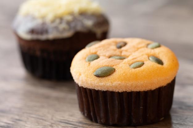 Mamon-kuchen oder -kleiner kuchen auf hölzernem schreibtischhintergrund
