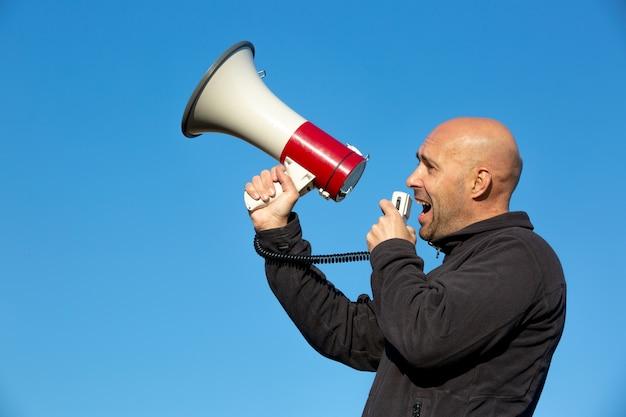 Man acivist dämonenstarter schreit, schreit zum megaphon während eines riesigen demonstrationsereignisses, einer wirtschaftskrise, arbeitslosigkeit