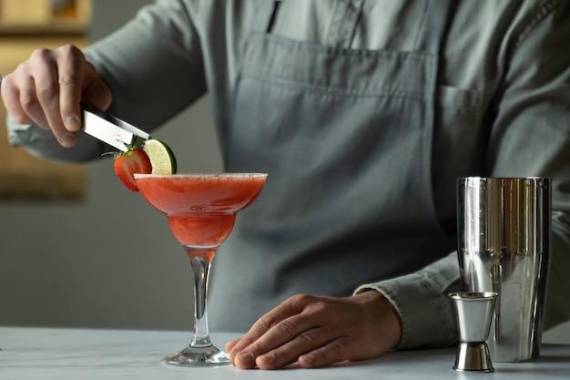 Man barkeeper bereitet einen margarita-cocktail zu und dekoriert das glas mit limette und erdbeeren