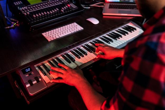Man compositor spielt auf dem keyboard im plattenstudio für radio fm