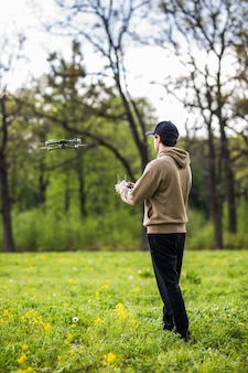 Man, der drohnen betreibt, die durch fernbedienung in der natur fliegen oder schweben