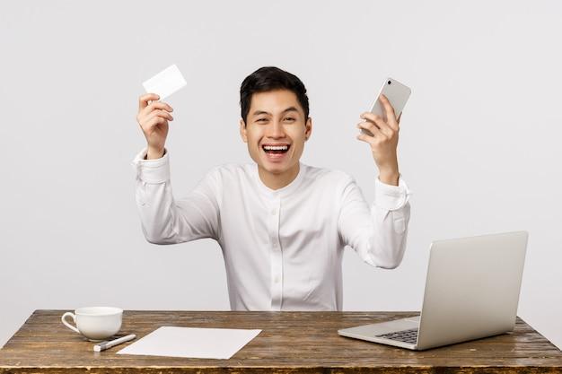 Man feiert, hurra ja geste, viel gemacht, nach bestem preis bestellt. der asiatische geschäftsmann, der hände anhebt, den smartphone und kreditkarte hält und fröhlich lächelt, las laptopanzeige der guten nachrichten