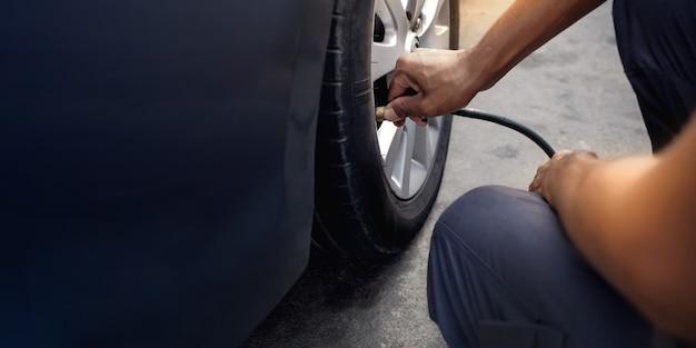 Man füllt luft in den reifen. autofahrer überprüfung des luftdrucks und der wartung