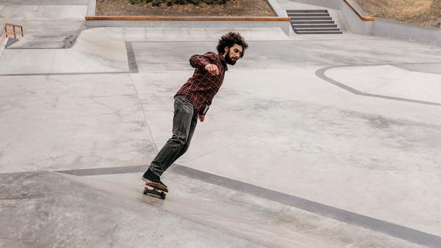 Man genießt das skateboarden draußen im park