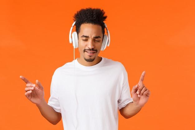 Man genießt tolle beats. attraktiver moderner hippie-afroamerikanerkerl mit dem afrohaarschnitt, dem schnurrbart, den nahen augen, die mit den fingern trommeln und hören die musik in den kopfhörern, orange