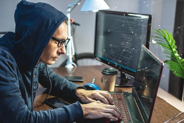 Man hacker in der haube programmiert virencode auf der tastatur für den laptop