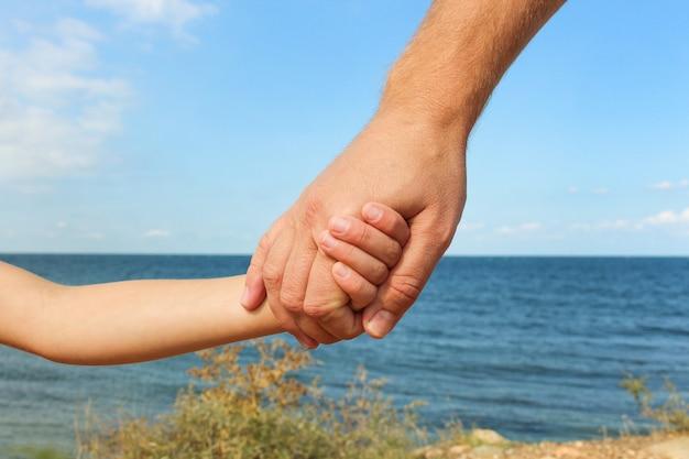 Man hält die hand des kindes auf den hintergrund des meeres und des himmels konzept der liebe, fürsorge, freundschaft, vertrauen in die familie.