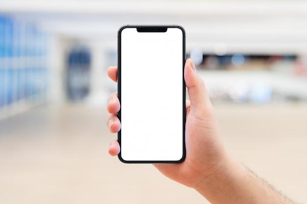 Man-hand, die den leeren weißen bildschirm des mobilen smartphones hält