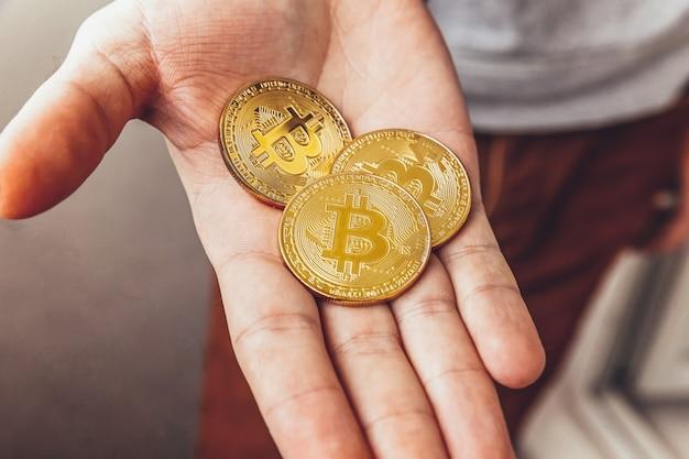 Man hand, die goldene bitcoin-münze der kryptowährung hält