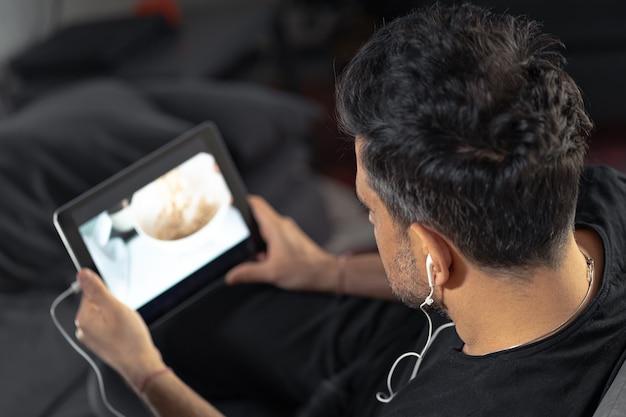 Man hand hält unter verwendung der digitalen tablette, die online-kochmeisterklasse unter verwendung der kopfhörer beobachtet. kochen aus der ferne lernen