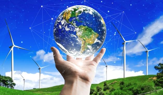 Man hand kümmert sich um den planeten erde mit umweltfreundlichem windturbinenpark und grüner erneuerbarer energie im hintergrund.