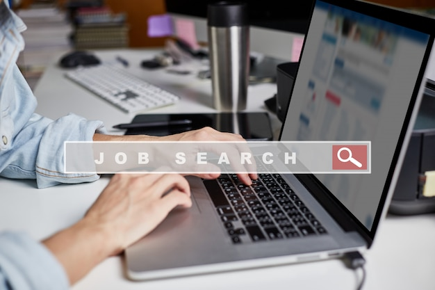 Man hand mit laptop browsing arbeitsmöglichkeiten online unter verwendung der jobsuche auf der internet-website zu hause