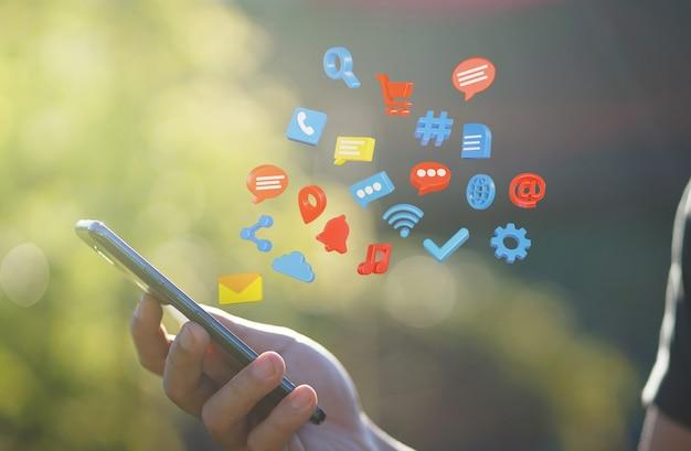 Man hand mit smartphone mit technologie-symbol benachrichtigung fliegen