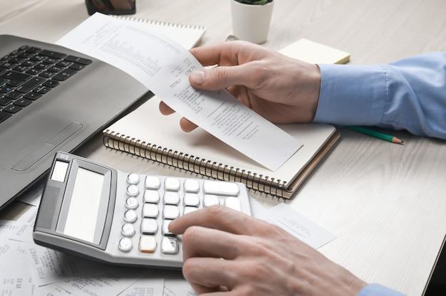 Man hand mit taschenrechner und schreiben notieren mit berechnen über kosten und steuern im home office. geschäftsmann, der einige papiere am arbeitsplatz erledigt