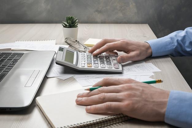 Man hand mit taschenrechner und schreiben notieren mit berechnen über kosten und steuern im home office.