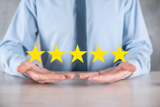 Man hand smartphone zeigt auf fünf sterne ausgezeichnete bewertung. zeigen fünf sterne symbol, um die bewertung des unternehmens zu erhöhen. überprüfen, erhöhen sie die bewertung oder das ranking, bewerten und klassifizieren sie das konzept