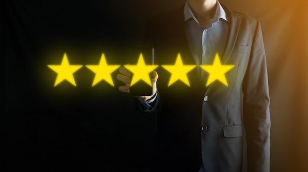 Man hand zeigt auf fünf sterne ausgezeichnete bewertung. zeigen von fünf sternen symbol, um die bewertung des unternehmens zu erhöhen. überprüfung, erhöhung der bewertung oder rangfolge, bewertung und klassifizierungskonzept.