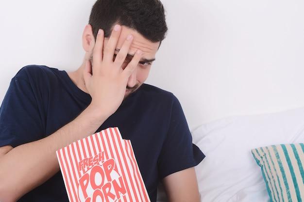 Man isst popcorn und schaut filme.