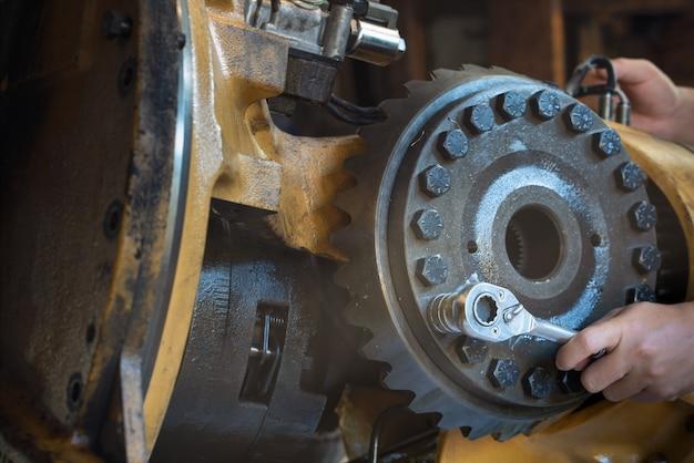 Man kann einen schraubenschlüssel verwenden, um die schraube des hinterrads am getriebe zu lösen
