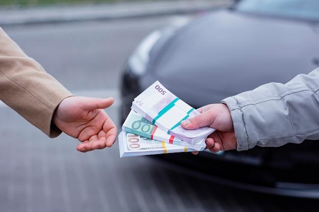 Man kauft ein modernes auto und übergibt dem verkäufer ein bündel dollar und euro.
