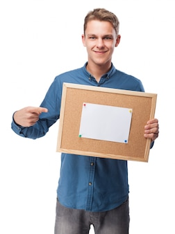 Man lächelt mit einem leeren papier auf einem brett