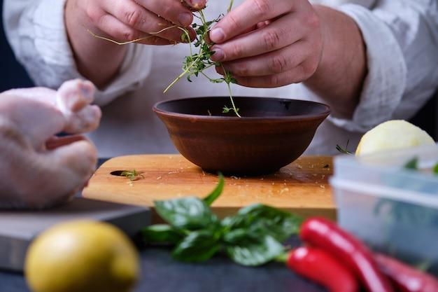 Man legt thymian in einen teller. der prozess des kochens von hühnchen mit kräutern, gewürzen und zitrone im ofen.