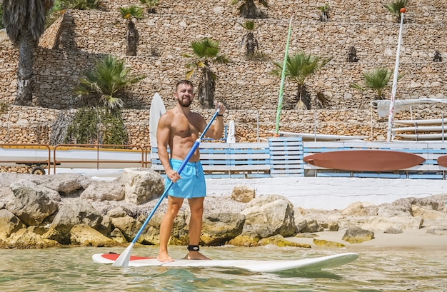 Man lernt paddle-boarding im wasser