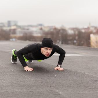 Man macht push-ups auf dem dach