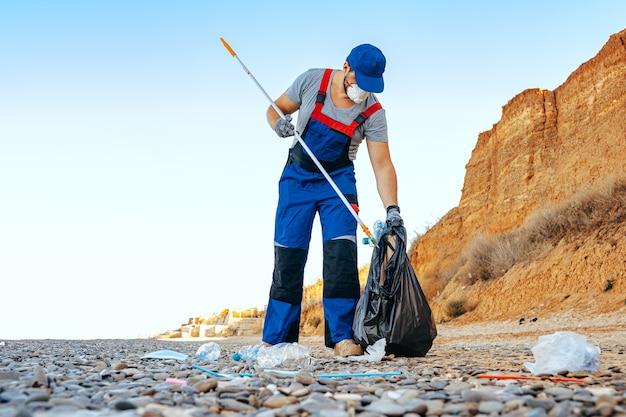 Man meldet sich freiwillig in kalifornien und sammelt müll am strand mit einem reach extender stick