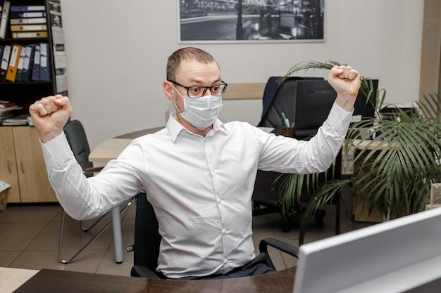 Man n schutzmaske, die laptop betrachtet, der durch gute coronovirus-nachrichten aufgeregt wird