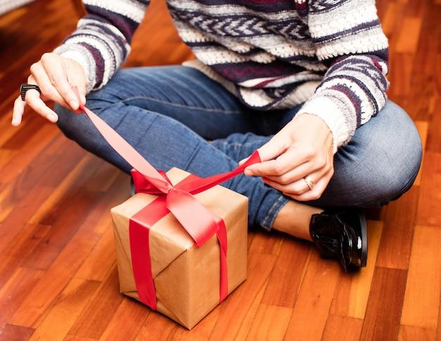 Man öffnet ein geschenk auf dem boden sitzen