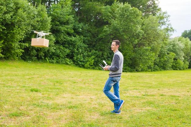 Man operating drohne fliegt oder schwebt per fernbedienung in der natur