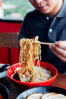 Man packe die ramen-nudel aus der schüssel von essstäbchen von shoyu chashu ramen durch seine hand.