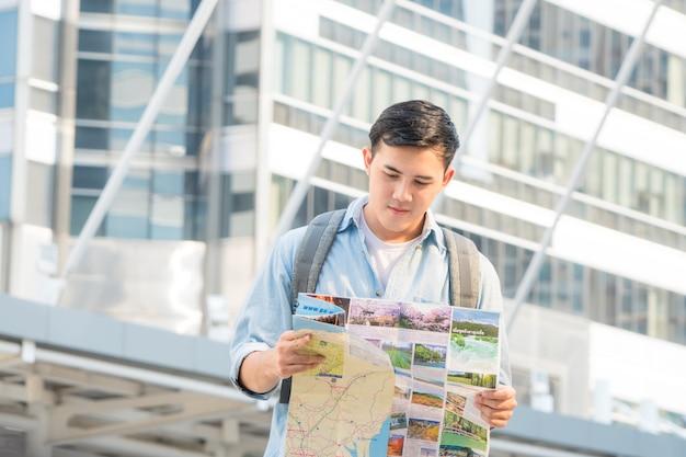 Man people backpacker verwenden eine generische lokale karte und suchen nach einem gebäude für attraktionen.