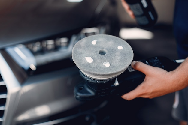 Man poliert ein auto in einer garage