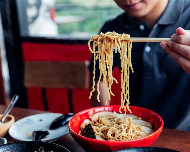 Man rag ramen nudel aus der schüssel von stäbchen aus shoyu chashu ramen von seiner hand.