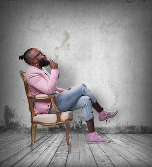 Man raucht eine zigarre auf einem stuhl sitzt