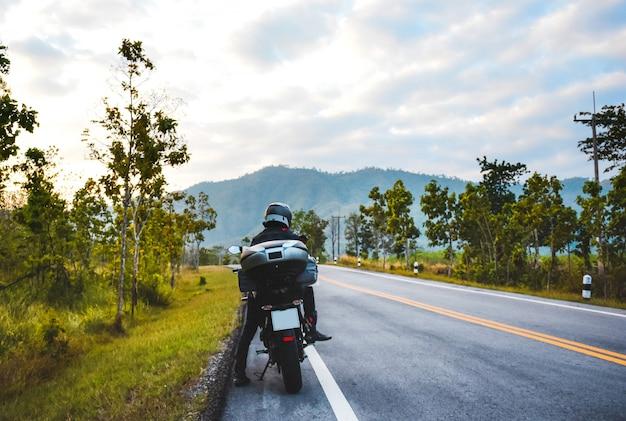 Man reist mit motorrad, radfahrer und landschaft