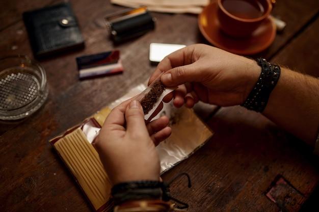 Man rollt eine zigarette, holztisch im hintergrund. tabakrauchkultur, spezifischer reicher geschmack. männliche raucher freizeit im büro